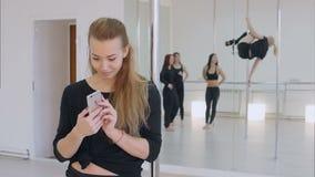 Ballerino sveglio del palo che per mezzo del telefono cellulare durante la classe di ballo del palo archivi video