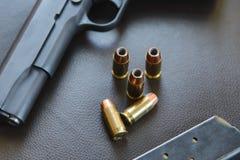 45 balles creuses de point de calibre s'approchent du pistolet et de la magazine sur le le Image stock