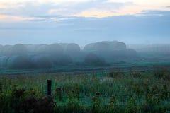 Balles de foin empilées avec la brume de matin autour de eux photo stock