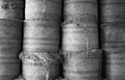Balles de foin rondes empilées dans une grange, noire et blanche Photos libres de droits