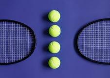 Balles de tennis et deux raquettes de tennis noires Fond violet Image stock