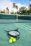 Balles de tennis et raquettes sur la cour Photographie stock libre de droits