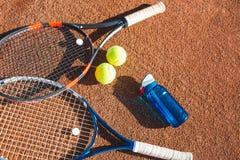 Balles de tennis et raquettes sur la cour Photographie stock