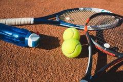 Balles de tennis et raquettes sur la cour Photo stock
