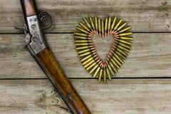 Balles sous forme de coeur à côté de fusil sur le fond en bois rustique Images stock