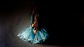Ballet. A blue velvet romantic tutu is hanging on a old wall in dark dressing room with a worn pair of ballet pointe shoes with copy or text space royalty free stock photo