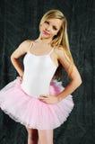 Ballet. Young female ballet dancer wearing her tutu and leotard standing aginst a black backdrop Stock Images