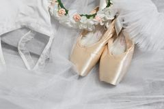 Ballet accessories. Pointe shoes, white ballet tutu, a wreath of flowers. Concert costume Sylphides. Preparation for performance royalty free stock photo
