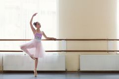 Young ballerina standing on poite at barre in ballet class. Ballet background. Young ballerina standing on poite at barre at dance class, copy space stock photos