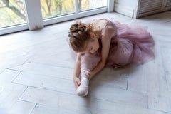 Ballet-bailarín joven que se sienta en el piso Imagenes de archivo