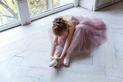 Ballet-bailarín joven que se sienta en el piso Foto de archivo