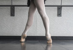The Ballet Barre. A ballerina in fourth position on releve at the barre Stock Photography