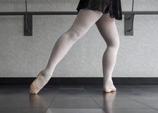 Ballet Barre Work. A ballet dancer at the barre doing a tendu derriere on fondu Stock Image