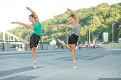 Ballet in the city. Two young beautiful twin sister dancing ballet in the city with ballet costume. urban sync dance. industrial street dancing. with special stock photography