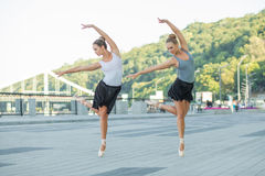 Ballet in the city. Two young beautiful twin sister dancing ballet in the city with ballet costume. urban sync dance. industrial street dancing. with special Stock Images