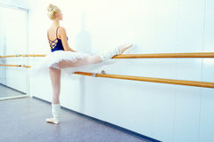 Ballet class. Beautiful ballet dancer training near the ballet barre in a ballet class royalty free stock image