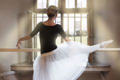In ballet class-room. Black silhouette of a ballet dancer in position at the barre near the window stock photo