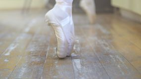Ballet.Close-up of a girl`s legs in white ballet shoes during ballet training. Element of classical dance. 4K