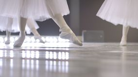 Ballet. Close-up of a girl`s legs in white ballet shoes during ballet training. Element of classical dance. 4K.