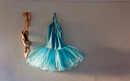 Ballet costume on old wall. A blue velvet romantic tutu is hanging on a old wall in dressing room beside a worn pair of ballet pointe shoes with copy or text Royalty Free Stock Photos