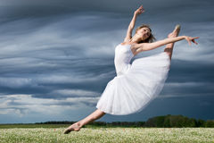 Ballet dancer. Large step of beautiful ballet dancer against cloudy sky stock images