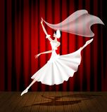 Ballet dancer. Against the background of the stage and red curtain dancing ballerina in a white dress Stock Photos