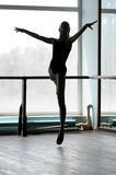 Ballet dancer in arabesque position. Silhouette of a ballerina making arabesque in the air. Shot against the window with sunlight Stock Images