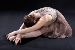 Ballet dancer bending forward. A ballerina bending forward while practising in an elegant costume Stock Photos