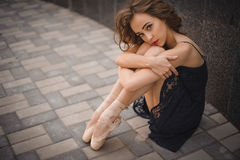 Ballet dancer in black dress and pointe shoes sitting on the ground Royalty Free Stock Photo