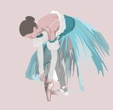 Ballet. Dancer in blue dress ties up ballet shoes Royalty Free Stock Images