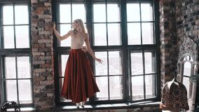 Ballet dancer in a bright red skirt on the background of the window stock footage