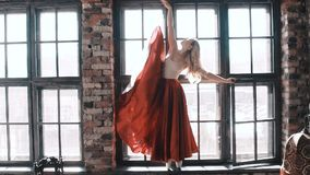 Ballet dancer in a bright red skirt on the background of the window stock video footage