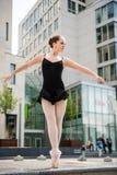 Ballet dancer dancing on street. Ballet dancer (ballerina) dancing on street with business buildings in background Stock Photography