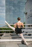 Ballet dancer dancing on street. Ballet dancer (ballerina) dancing on street with business buildings in background Royalty Free Stock Image