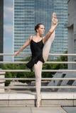 Ballet dancer dancing on street. Ballet dancer (ballerina) dancing on street with business buildings in background Stock Photo