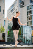 Ballet dancer dancing on street. Ballet dancer (ballerina) dancing on street with business buildings in background Royalty Free Stock Images