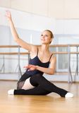 Ballet dancer does exercises sitting on the wooden floor stock photography