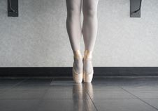 Ballet dancer En pointe in her dance shoes. En releve at the dance studio royalty free stock photography