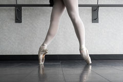 Ballet Dancer En Pointe in 4th. Ballerina at the barre warming up her feet and pointe shoes Stock Photos