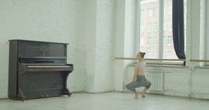 Ballet dancer exercising grand plie at barre. Graceful classic ballet dancer performing grand plie exersice at barre during rehearsal while training elements of stock footage