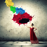Ballet dancer in flying satin dress with umbrella. Under the paint stock photo
