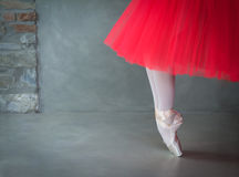 Ballet dancer legs with pointe shoes and coral tutu. Space for text stock image