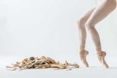 Ballet dancer legs and pointe shoes. Many beige pointe shoes on the light background in the studio. Next to it there are ballerina`s legs on the pointes in beige royalty free stock photography
