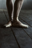 Ballet dancer legs in pointes standing on the black floor Royalty Free Stock Photos
