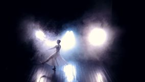 A ballet dancer makes high jumps through a dark stage. stock footage