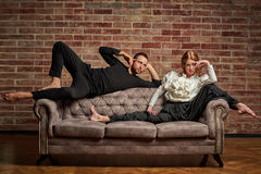 Ballet dancer and male latin dancer in contemporary style. Female ballet dancer and male latin dancer in contemporary style in pose lie on the sofa Stock Image