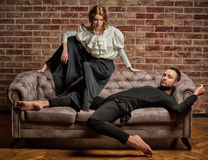 Ballet dancer and male latin dancer in contemporary style. Female ballet dancer and male latin dancer in contemporary style in pose lie on the sofa Royalty Free Stock Photos