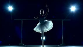 Ballet dancer near training machine. slow motion. Legs dancers on white pointe, near the choreographic training machine. Young ballerinas. Silhouette, blue stock footage