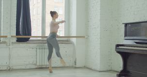Ballet dancer performing pounte exercise at barre. Charming graceful ballerina rehearsing in ballet studio, performing pounte exersice at barre. Elegant classic stock footage