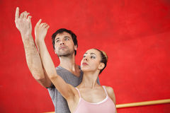 Ballet Dancer Performing With Trainer Against Red Wall. Young female ballet dancer performing with male trainer against red wall at studio Stock Photos